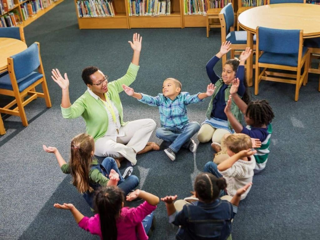 elementary school kids in a restorative circle with hands in the air
