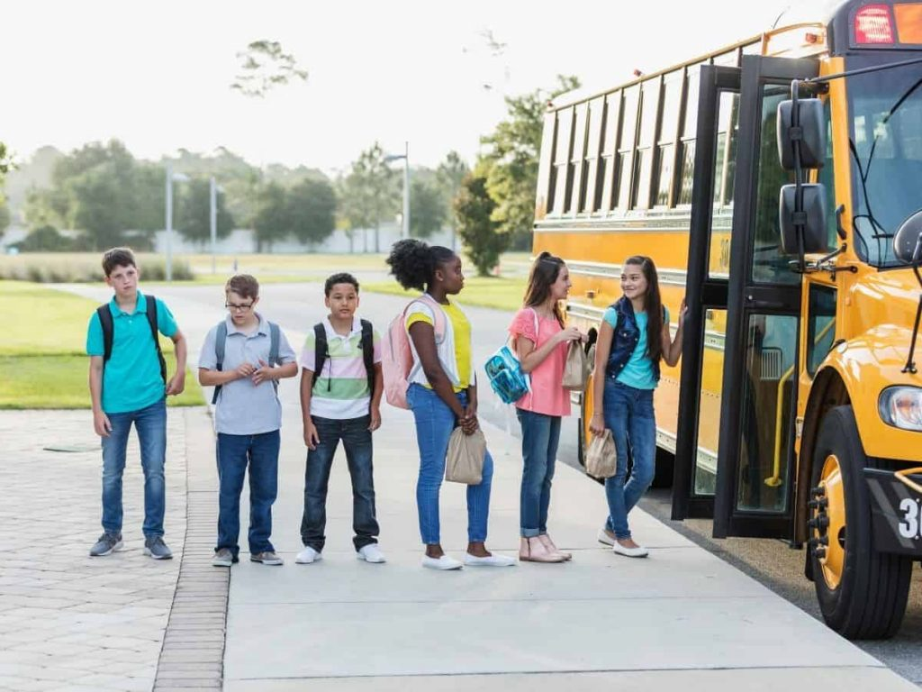 middle schoolers lined up at a school bus