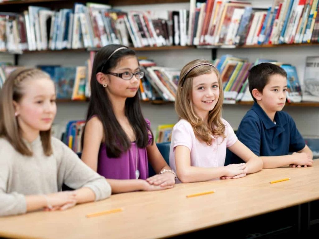 kids in class smiling with hands folded on desk