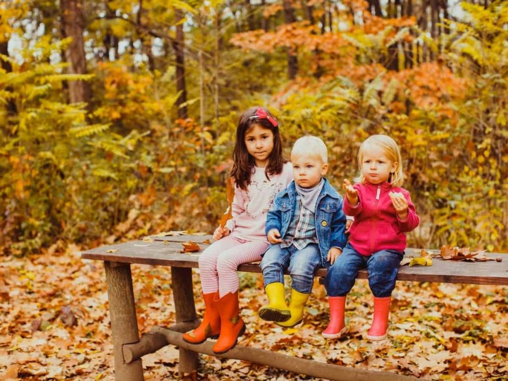 kids in autumn sitting on a bench