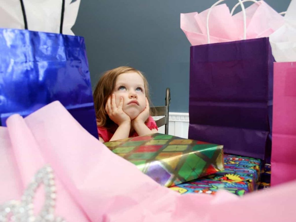 ungrateful child annoyed or bored with her pile of birthday gifts