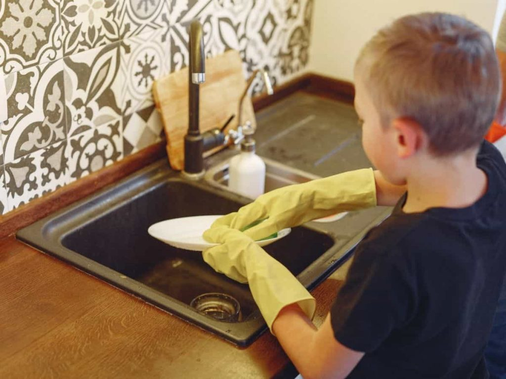 kid doing the dishes - skipping chores makes for an ungrateful child